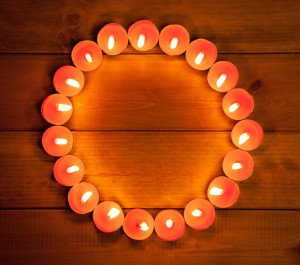candles glowing in circle shape on golden wood background